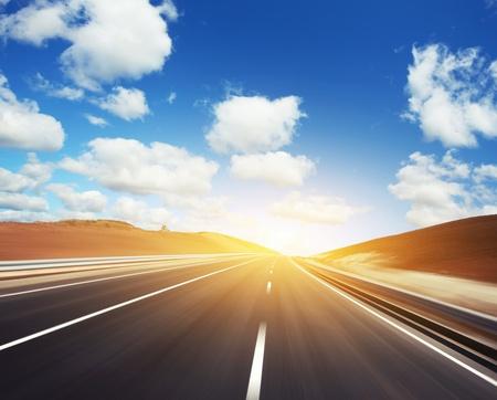 Bewegung verwischt Asphaltstraße und bewölkten blauen Himmel