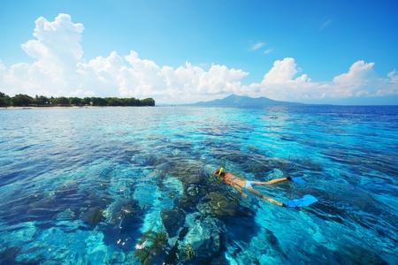 Tropische blauwe zee en jonge vrouw snorkelen boven rif Stockfoto
