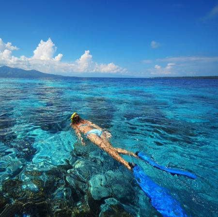 Mar azul tropical y snorkeling en los arrecifes joven