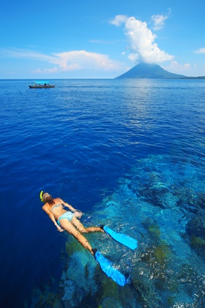 indonesia girl: Tropical blue sea and young woman snorkeling over reef