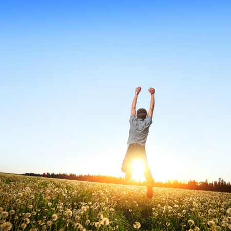 Young man jumping on a meadow with dandelions Stock Photo - 11149582