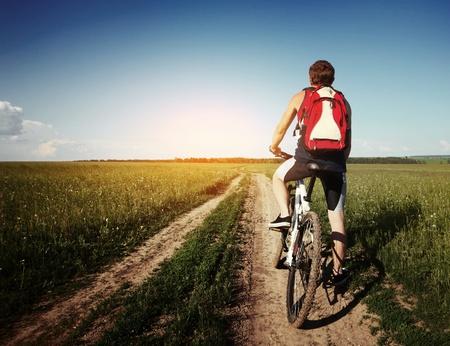 young man standing: Giovane uomo in piedi con bycycle su una strada di campagna