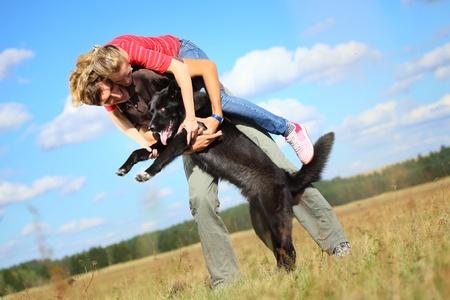 Familia jóvenes se divierten con su perro grande en un prado campo.