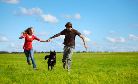 Young happy family running with dog on a green meadow photo