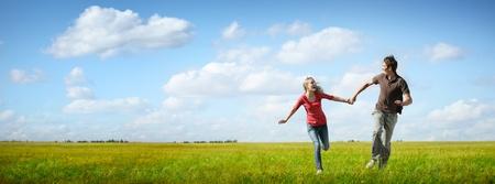 Feliz pareja de jóvenes corriendo en un prado verde con el cielo nublado azul en el fondo