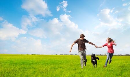 mujer con perro: Feliz pareja de jóvenes corriendo en un prado verde con un perro negro