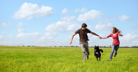 Feliz pareja de jóvenes corriendo en un prado verde con un perro negro
