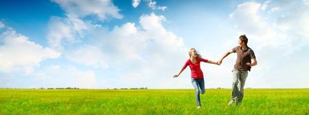 gente feliz: Feliz pareja joven que se ejecuta en un prado verde con el cielo nublado azul en el fondo