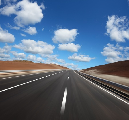 middle of the road: Motion blurred asphalt road and cloudy blue sky