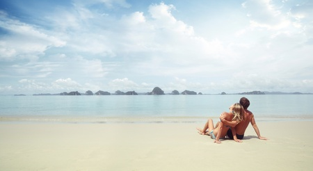 Young couple sitting on a resorts fine sand and looking to a sea  photo