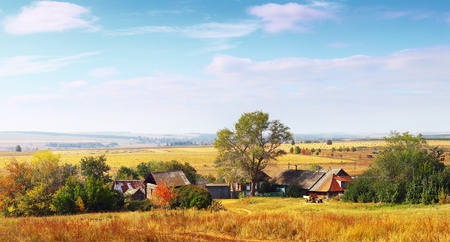 Village with wooden houses among autumn fields at sunny day photo