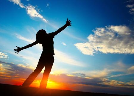 manos levantadas: Mujer joven con las manos levantadas en el fondo cielo del atardecer