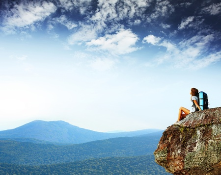 Young woman with backpack sitting on cliff's edge and looking to a sky Foto de archivo