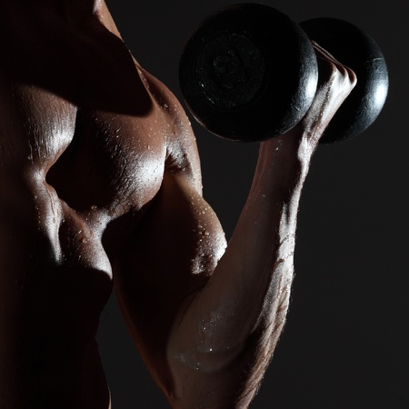 perspiration: Part of a wet mans body with metal dumbbell on a gray background Stock Photo