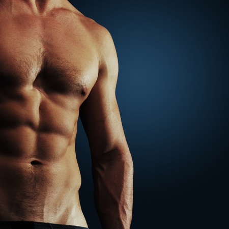 pectoral: Part of a mans body on a dark blue background Stock Photo