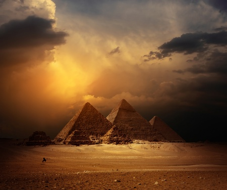 Great pyramids in Giza valley with yellow dark clouds on the background photo