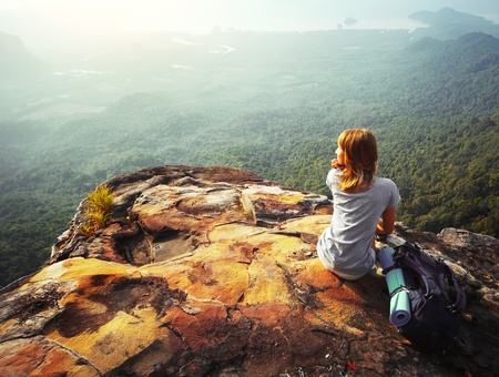cima montagna: Giovane donna seduta su una roccia con zaino e guardando verso l'orizzonte Archivio Fotografico