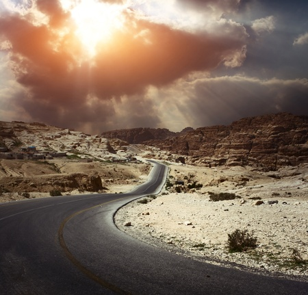 Asphalt road in a desert with dark cloudy sky on the background