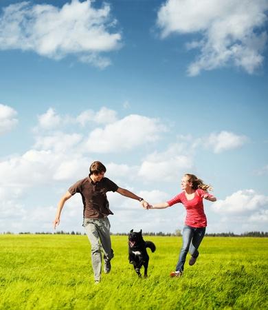 perro corriendo: Pareja joven feliz corriendo en un prado verde con un perro