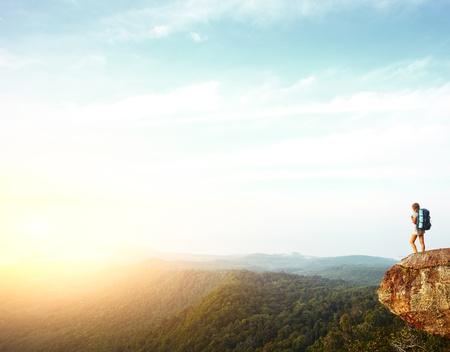 mujer mirando el horizonte: Joven mujer de pie con mochila en borde del acantilado y mirando hacia el horizonte