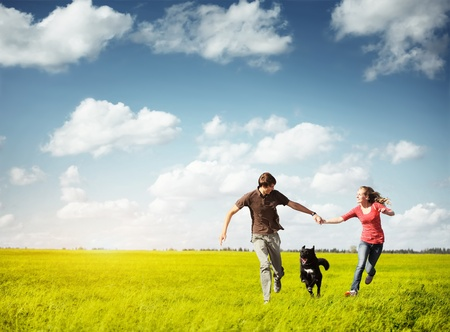 Young happy couple runnig on a green meadow with a dog photo