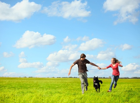 Young happy couple running on a green meadow with a dog photo
