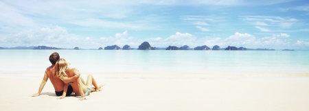 Young couple sitting on a resorts white sand and looking to a far islands on the horizon photo