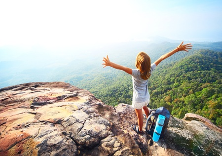 altitude: Young woman standing with backpack on cliffs edge and looking into a wide valley Stock Photo