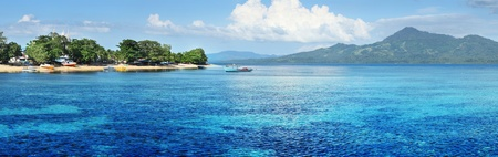 Bunaken island (left) with boats and wooden buildings in trees. North Sulawesi. Indonesia