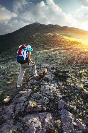 Young sporty woman with backpack walking through rocky land to the top a mountain photo