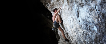 Young semi naked man climbing on a rock without belay photo