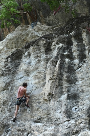 Young semi naked man climbing on a rock with belay photo
