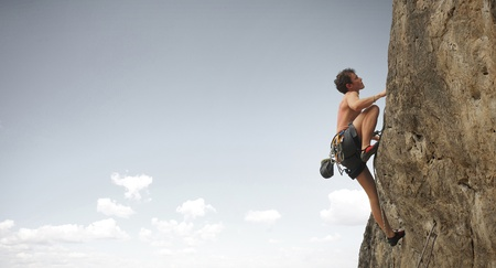 climber: Young man climbs on a cliff on grey sky background