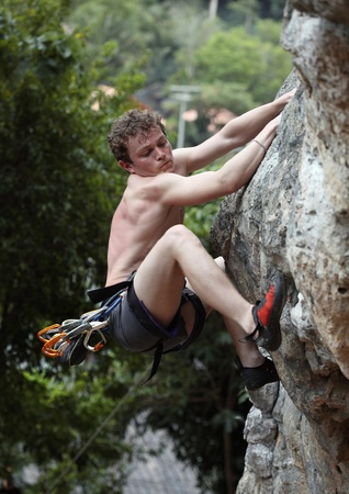 Young climber on a rocky wall. Face with effort emotions photo