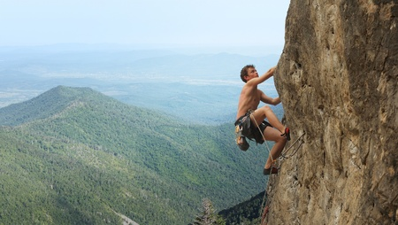 Young man climbs on a rocky wall in a valley with mountains photo