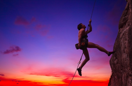 Young man hanging on a rope by a rocky wall over sunset sky background photo