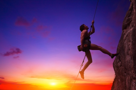 Young man hanging on a rope by a rocky wall over sunset sky background Stock Photo - 11540944
