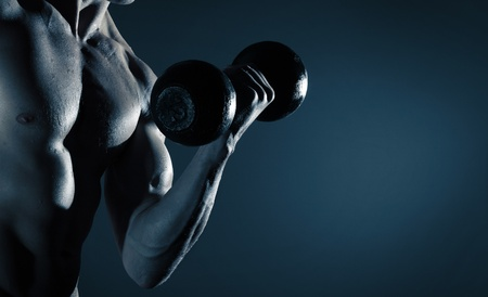 perspiration: Part of a mans body with metal dumbbell on a gray background Stock Photo