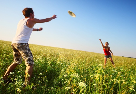 Young couple playing frisbee on a green meadow with grass on clear blue sky background. Focus on a woman, man is motion blured photo