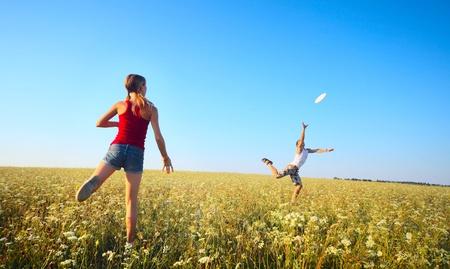 젊은 부부는 맑고 푸른 하늘 배경에 잔디 녹색 초원에 원반을 재생