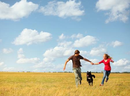 perro corriendo: Feliz pareja joven runnig en un prado con un perro Foto de archivo