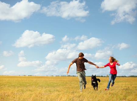 man jump: Young happy couple runnig on a meadow with a dog Stock Photo