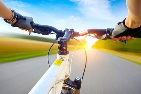 andando en bicicleta: Las manos en los guantes de la celebraci�n del manillar de una bicicleta. Movimiento borroso carretera de asfalto Foto de archivo