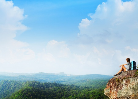 Young woman with backpack sitting on a rock and looking to the horizon Stock Photo