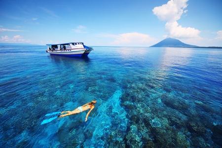 arrecife: Buceo Mujer joven en el mar transparente poco profunda cerca de la barca Foto de archivo