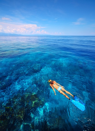Young woman snorkeling in transparent shallow blue sea above coral reef. Stock Photo - 11540758