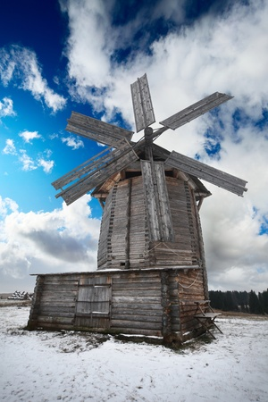 Old traditional windmill on snowy field and blue cloudy sky on the background photo