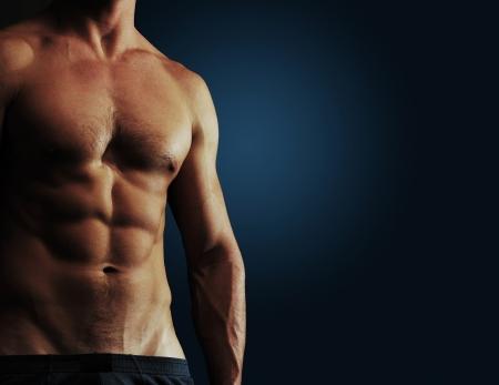 musculoso: Parte del cuerpo de un hombre sobre un fondo azul oscuro con copyspace