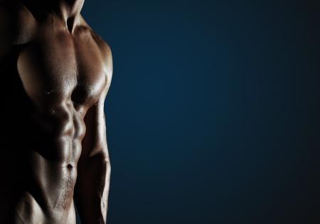 musculoso: Parte del cuerpo de un hombre h�meda sobre un fondo azul oscuro con copyspace