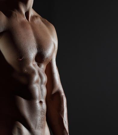 hombres musculosos: Parte del cuerpo de un hombre en h�medo sobre un fondo gris Foto de archivo